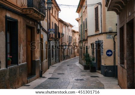 Port de Soller, Mallorca, Spain - May 24, 2016: Narrow winding streets in historical town part of Pollensa with its traditional stone houses, Mallorca, Spain