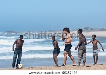 PORT ELIZABETH - MAY 02: black and white boys play soccer in the humewood beach. the country in june 2010 will host the world cup of soccer, may 02 2010 in Porth Elizabet, South Africa - stock photo