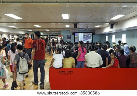 PORT KLANG, MALAYSIA - OCTOBER 1:Visitors at the MV Logos Hope theater room on October 1, 2011 in Port Klang, Malaysia. The 132.5m ship host the world's biggest floating book fair with 5000 book title - stock photo