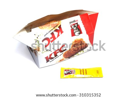 PORT-LOUIS, MAURITIUS - August ?19, 2015: Kentucky Fried Chicken Box with honey mustard sauce packet on white, KFC is the worlds second largest restaurant chain - stock photo