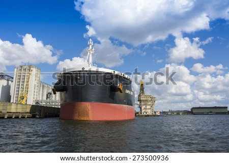 Port of Amsterdam, Noord-Holland/Netherlands - April 28-04-2015 - Bulk carrier Darya Devi is moored in the Vlothaven and is busy with cargo operations at the quay of IGMA. Cloudy sky background. - stock photo