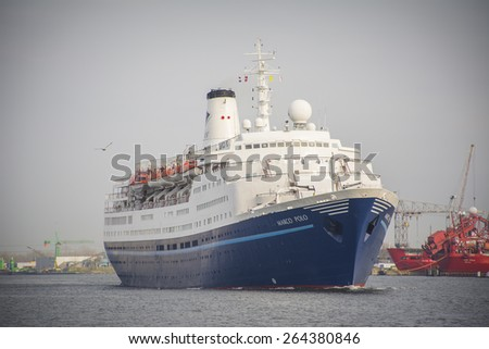 Port of Amsterdam, Noord-Holland/Netherlands - March 28-03-15 - Cruise ship Marco Polo is sailing by sunrise to the Passenger Terminal Amsterdam. Damen ship repair on the background. - stock photo