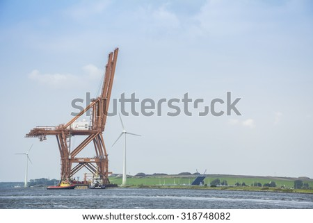 Port of Amsterdam, Noord-Holland/Netherlands - September 20-09-2015 - Last CERES cranes leaving the port of Amsterdam on a barge. The cranes were used by the ACT (Amsterdam Container Terminal).