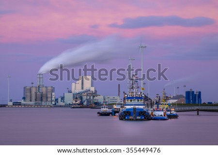 Port of Eemshaven with ships at the quay and heavy industry in the backdrop - stock photo