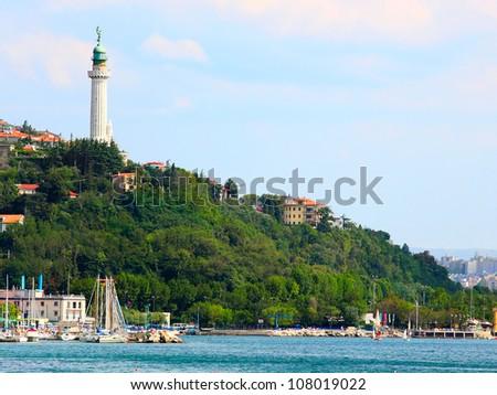 Port of Trieste with Faro della Vittoria, or Victory Lighthouse. Adriatic sea, Italy, Europe. - stock photo