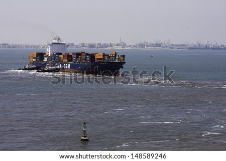 PORT SAID, EGYPT - MAY 11 : tug boats try to pull out container ship CMA CGM ONYX which is aground on the approaching channel to Suez Canal. Port Said, Egypt, entrance to Suez Canal on May 11, 2013 - stock photo