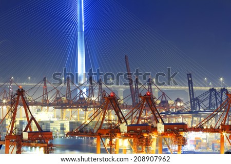 Port warehouse with containers and industrial cargoes at night - stock photo