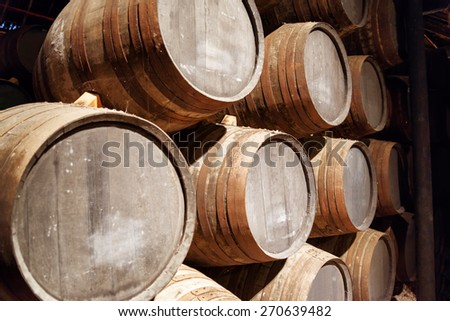 Port wine from the vineyards Douro Valley in Portugal aging in oak barrels stacked in the old cellar. Product of organic farming. - stock photo