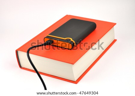 Portable disk on a thick book - stock photo