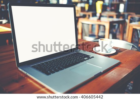 Portable laptop computer and cup of coffee lying on a wooden table in cafe bar interior, open net-book with copy space screen for your information content or text message, freelance remote job - stock photo