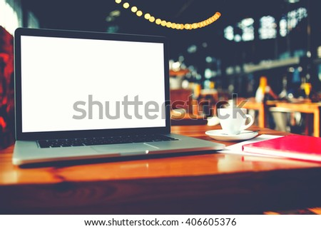 Portable laptop computer with blank copy space screen for text message or promotional content, net-book and notepad lying on table in cafe bar interior, distance work via internet during coffee break - stock photo