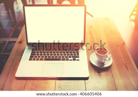Portable net-book with blank copy screen screen for your information content or text message, laptop computer lying on wooden table in cafe bar interior,freelance work via internet during coffee break - stock photo