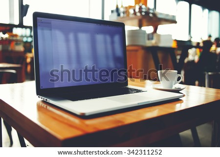 Portable net-book with copy space screen for your text massage or promotional content, open laptop computer and cup of hot drink lying on a wooden table in cafe interior, freelance work in internet  - stock photo