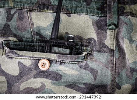 Portable radio in a pocket of pants with camouflage pattern. Toned. - stock photo