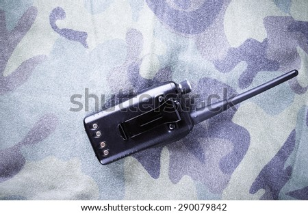 Portable radio on a fabric with camouflage pattern. Toned. - stock photo