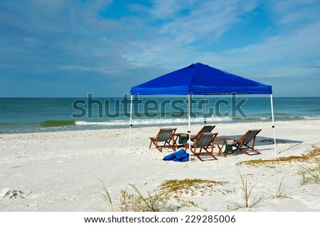 Portable Shelter with Lounge Chairs and Tables Set up on the Beach  - stock photo