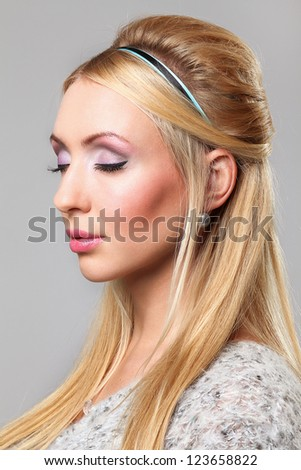 Portait of beautiful young woman with make-up over grey background - stock photo