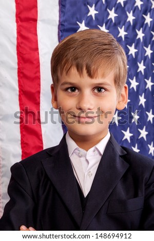 Portait of Caucasian boy  with American flag in background.