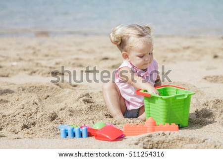 portait of little girl playing sand toys at the beach with copy space