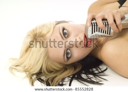 Portait of pretty woman or girl music singer lying down with microphone on white - stock photo