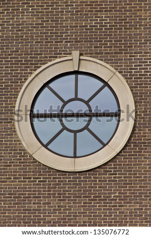 Portal style window on brick wall with clear blue sky reflected in window.