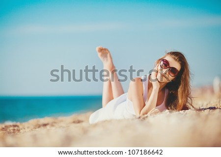 Portarait of young beautiful woman on the seashore sand