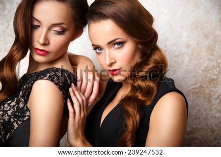 Portarit of beautiful twins young women in gorgeous evening dresses