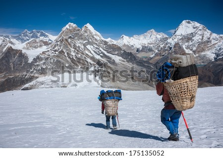 Porter carrying heavy loads in Himalayas of Nepal - stock photo