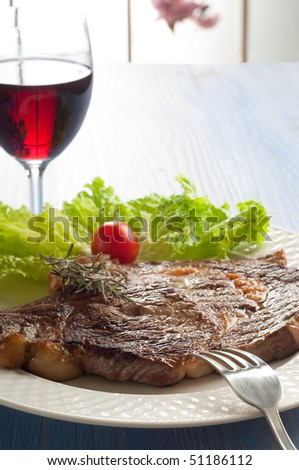 porterhouse with salad and wine