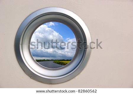 Porthole of a boat with nice view on a scenic landscape - stock photo