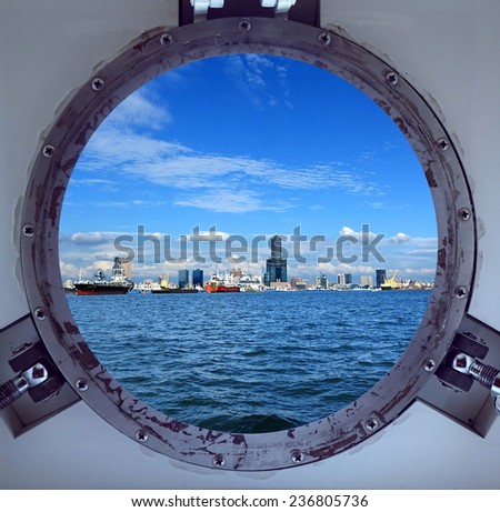 Porthole view of Kaohsiung Harbor and skyline on a bright summer day - stock photo