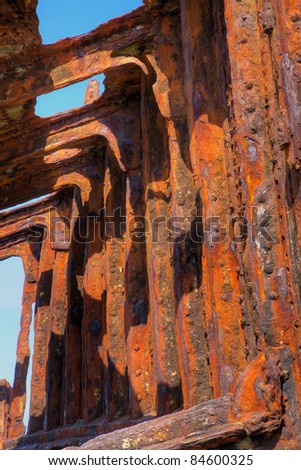 Portion of a red rusted hull of a shipwrecked hull - stock photo