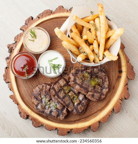 Portion of BBQ beef filet mignon steak  served  on wooden board with  ketchup, mustard and cream sauces, fried potatoes in aluminium bucket - stock photo