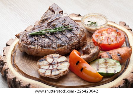 Portion of BBQ t-bone steak  served  on wooden board with  rosemary, mustard sauce  and grilled vegetables : tomato, carrot, paprika, garlic,  champignon,  zucchini - stock photo