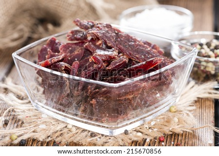 Portion of Beef Jerky (close-up shot) on vintage wooden background