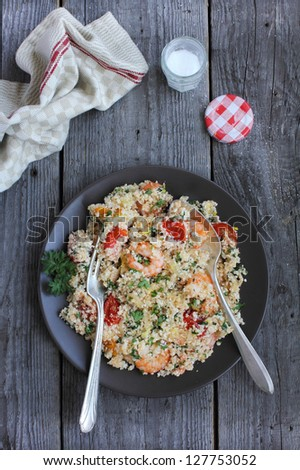 Portion of cauliflower couscous salad with roasted garlic shrimps, cherry tomatoes, lemon juice and zest and chopped fresh parsley in a plate ready to eat - stock photo
