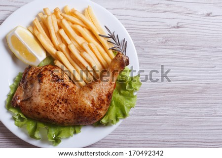 Portion of chicken legs, french fries on a white plate. top view - stock photo