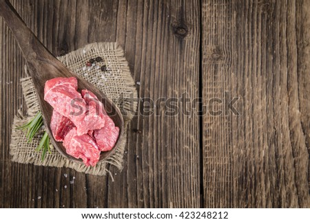 Portion of chopped Beef Steak (selective focus) on dark background - stock photo