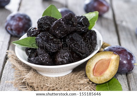 Portion of dried Plums on vintage woosen background - stock photo