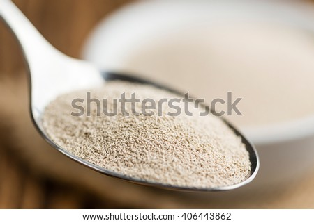 Portion of dried Yeast (close-up shot) on wooden background - stock photo