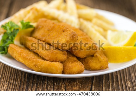 Portion of Fish Fingers (selective focus) on wooden background