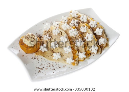 Portion of four pancakes stuffed with vanilla cream and peach, decorated with whipped cream and grated chocolate, served on a white plate. Isolated on white. - stock photo