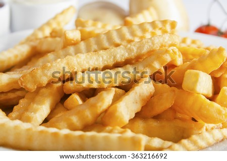 Portion of French fries (Crinkle-cut) deep fried, close up. - stock photo