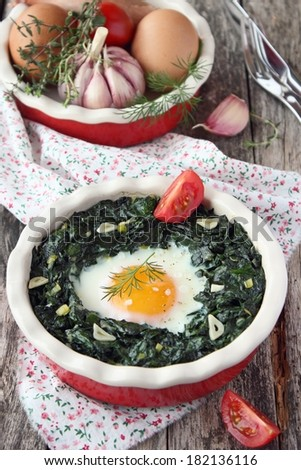Portion of fresh baked egg with spinach and tomatoes on wooden background. - stock photo