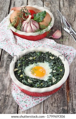 Portion of fresh baked egg with spinach on a rustic wooden table.  - stock photo