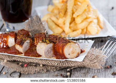 Portion of fresh made Currywurst with French Fries - stock photo