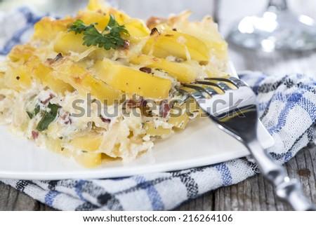 Portion of fresh made Potato Gratin on wooden background - stock photo