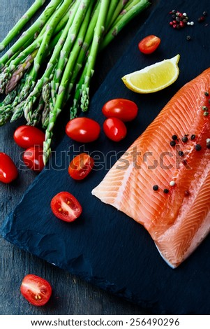 Portion of fresh salmon fillet with asparagus and aromatic herbs, spices and vegetables - healthy food, diet or cooking concept.  - stock photo