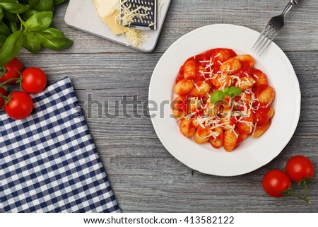 Portion of gnocchi in tomato sauce with cheese. - stock photo