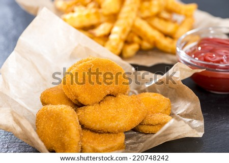 Portion of golden Chicken Nuggets with some french fries - stock photo